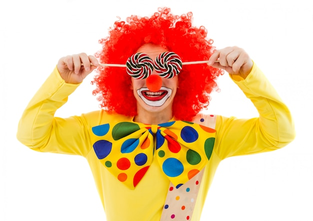 Portrait of funny playful clown in red wig covering his eyes Premium Photo