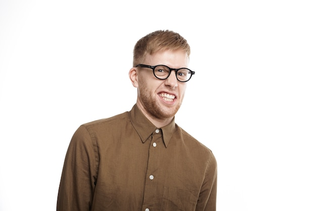 Portrait of funny young unshaven male in spectacles and brown shirt making wry face, clenching teeth while feeling disgusted because of smelling unpleasant bad stink, posing isolated Free Photo
