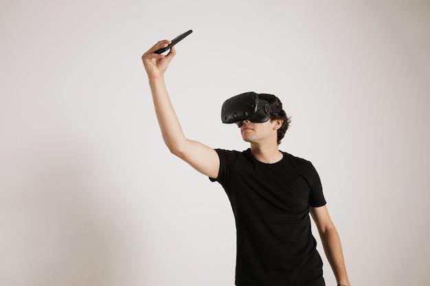 Ritratto di un giocatore in cuffia avricolare di vr e maglietta nera vuota che prende un selfie con il suo smartphone Foto Gratuite