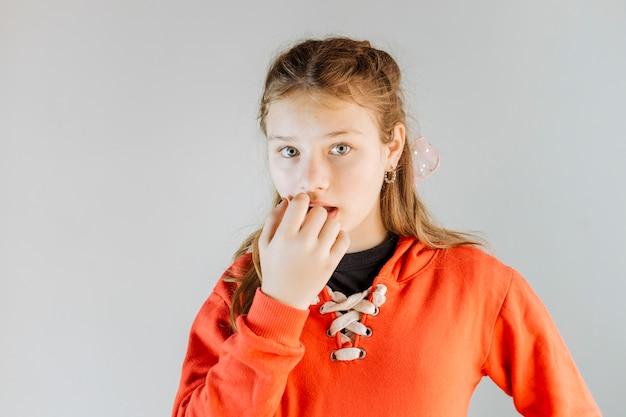 Portrait of a girl biting her fingernails Free Photo
