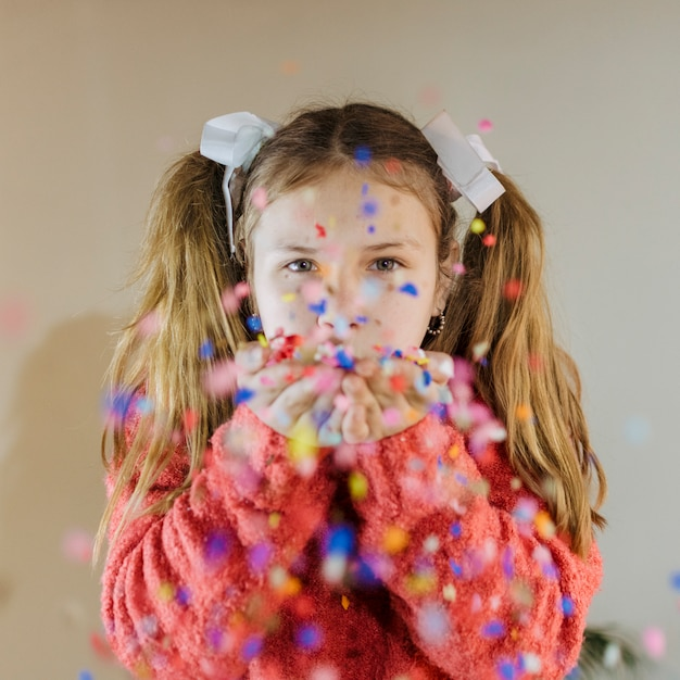 Portrait of a girl blowing confetti Free Photo