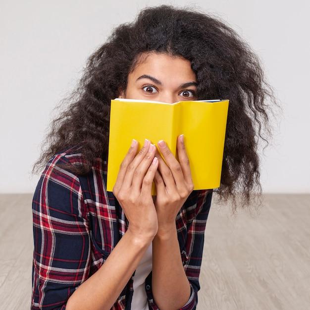 本で彼女の顔を覆っている肖像画の女の子 無料写真