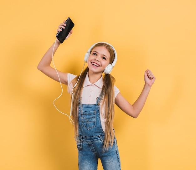 Portrait of a girl dancing while listening music on headphone through mobile phone against yellow backdrop Free Photo