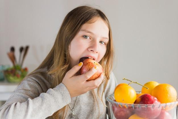 Ritratto di una ragazza che mangia mela rossa Foto Gratuite