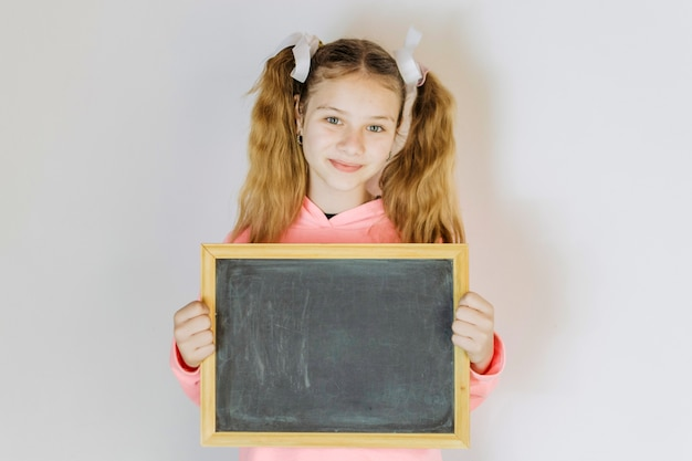 Portrait of a girl holding blank slate Free Photo