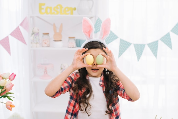 Portrait of a girl holding easter eggs in front of her eyes on easter day at home Free Photo