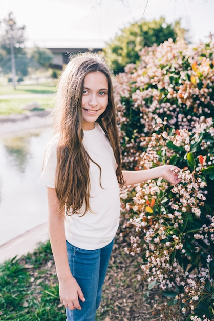 Portrait of a girl holding flowers on plant in park Free Photo