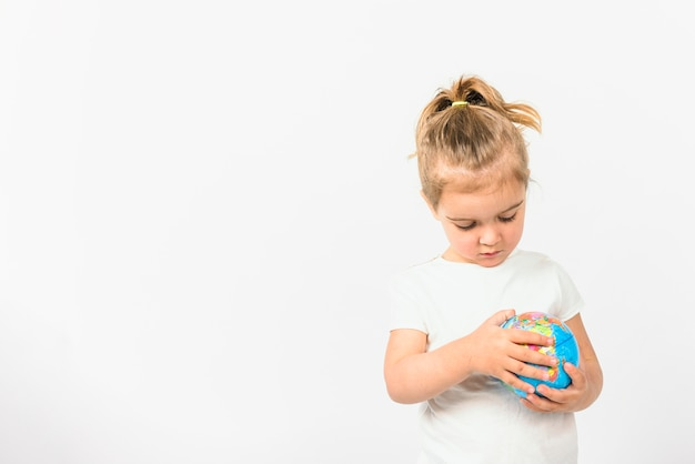 Portrait of a girl holding globe ball against white background Free Photo