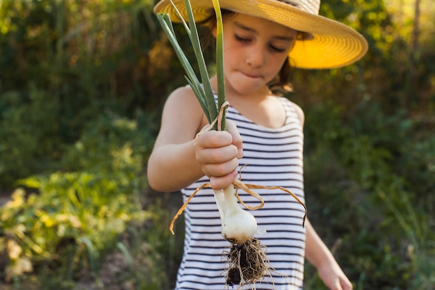Portrait of girl holding harvested spring onion Free Photo