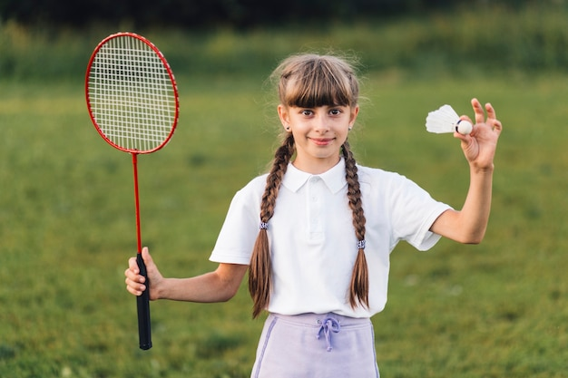 Portrait of a girl holding shuttlecock and badminton Free Photo