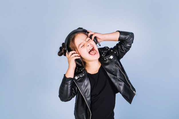 Portrait of a girl listening music on headphone laughing against blue background Free Photo