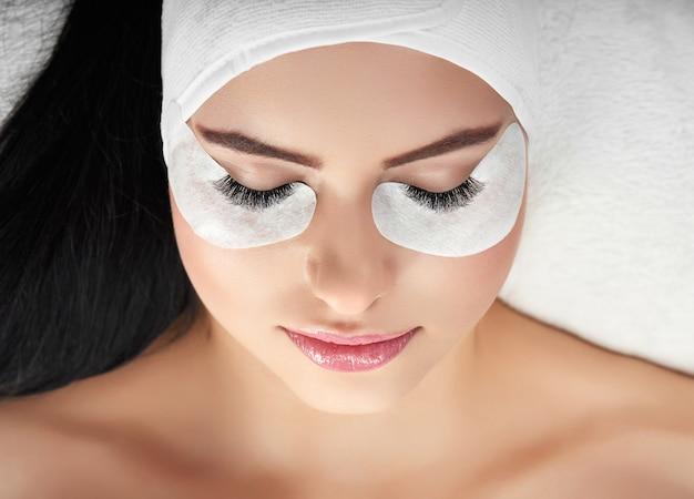 Portrait of girl lying during lashes enlarging. Premium Photo