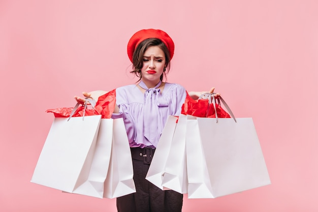 Ritratto di ragazza in berretto rosso guardando scontento di pacchetti con i vestiti. signora in camicetta lilla e pantaloni neri in posa su sfondo rosa. Foto Gratuite