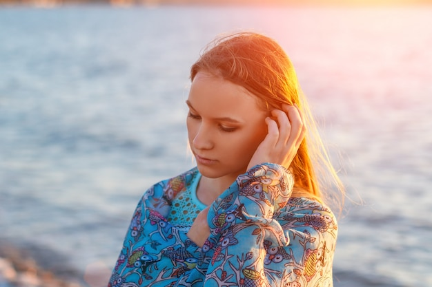 Portrait of a girl in the sea at sunset in rays of sun, vacation and relaxation Premium Photo