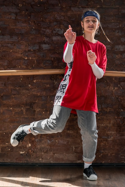 Portrait of a girl standing against brick wall dancing Free Photo