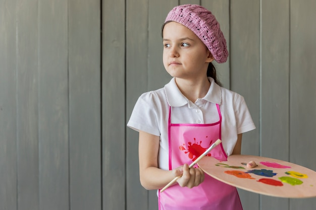 Portrait of a girl standing against wooden grey wall holding paint brush and palette Free Photo