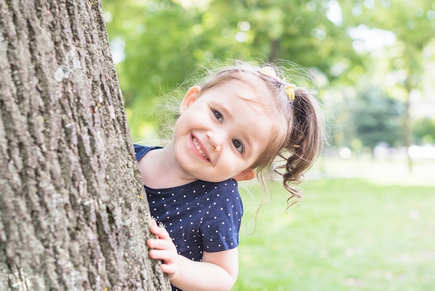 Portrait of a girl standing behind the tree peeking in the garden Free Photo