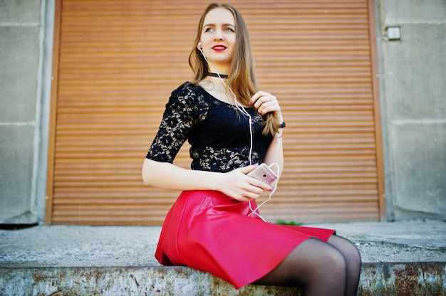 Portrait of girl with black choker on her neck, red leather skirt and mobile phone at hand with headphones against orange shutter. Premium Photo