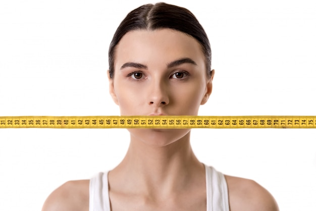 Portrait of girl with a tape measure in front of her mouth. diet concept Premium Photo