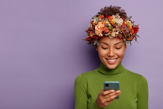 Il ritratto della modella autunnale felice indossa una ghirlanda autunnale decorativa, focalizzata sul dispositivo smartphone, legge buone notizie online, ha un'espressione felice del viso, modelli sul muro viola dello studio. Foto Gratuite