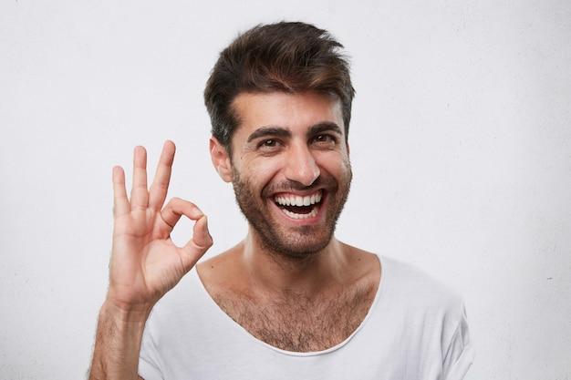 Ritratto di uomo barbuto felice con acconciatura alla moda che mostra segno giusto che esprime il suo accordo. giovane uomo d'affari bello che mostra il suo successo e che si rallegra del suo trionfo al lavoro gesticolando Foto Gratuite