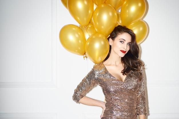 Ritratto di donna affascinante con palloncini dorati Foto Gratuite
