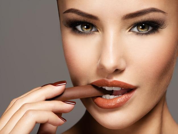 Ritratto di donna bella glamour tiene e mangia caramelle al cioccolato. Foto Gratuite