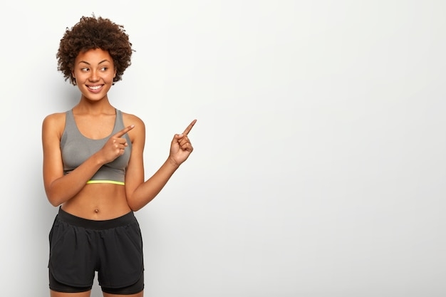 Portrait of good looking afro woman points away on blank space, smiles pleasantly, wears top and shorts, copy space against white wall Free Photo