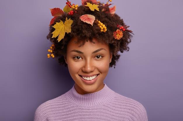 Ritratto di bella donna autunno fa il ritratto in studio, guarda felicemente la fotocamera, mostra i denti bianchi, ha i capelli ricci con piante autunnali, isolato contro il muro viola dello studio. Foto Gratuite