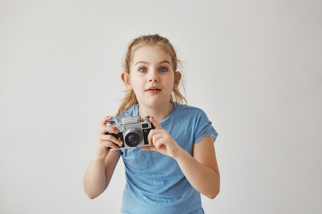 Free Photo Portrait Of Good Looking Blond Girl In Blue T Shirt Holding Camera In Hands With Concentrated Expression Going To Take A Picture Of Cute Cat On Street