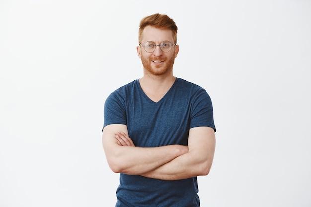Ritratto di un bel ragazzo maturo dai capelli rossi fiducioso con setole in occhiali rotondi, tenendo le mani sul petto e sorridendo ampiamente Foto Gratuite