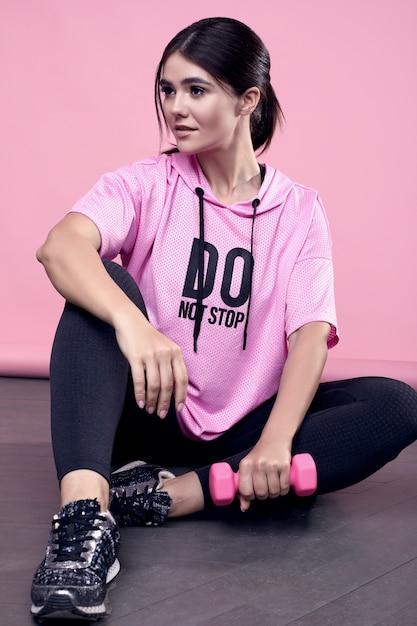 Ritratto di una donna latina positiva del corpo splendido in una felpa con cappuccio rosa di sport che si esercita con le teste di legno sul rosa Foto Gratuite