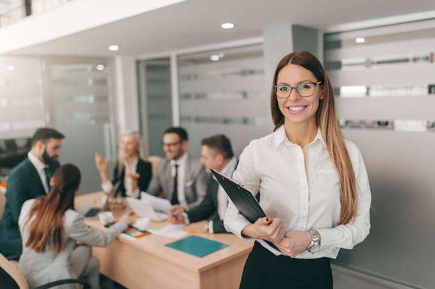 Portrait of gorgeous businesswoman in formal wear, with long brown hair and eyeglasses holding clipboard while standing at board room. Premium Photo