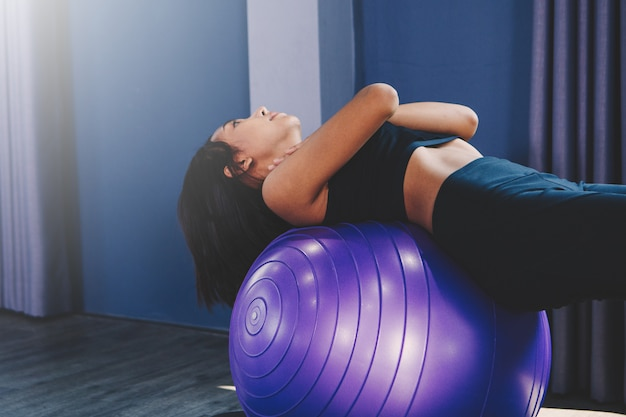 Portrait of gorgeous young woman practicing yoga indoor with ball Premium Photo