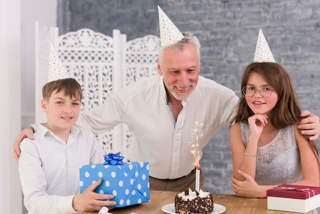 Portrait of grandchildren enjoying birthday party of their grandfather with cake and gift boxes Free Photo