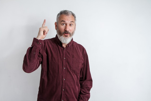 Portrait gray bearded man has an idea, pointing with index finger up isolated on white wall background Premium Photo