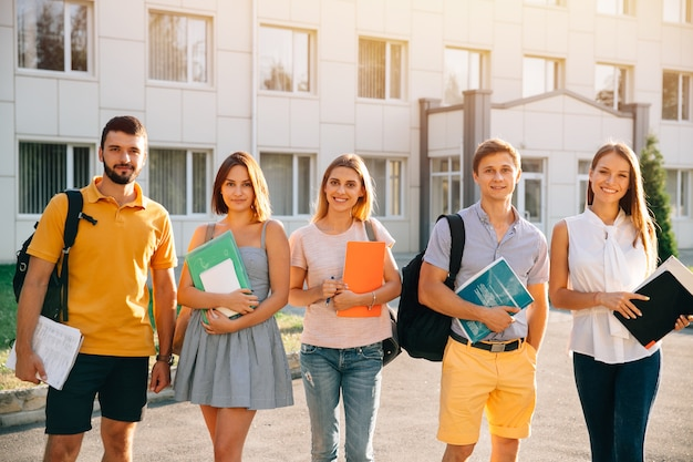 Portrait of group of happy students in casual outfit with books while standing Free Photo