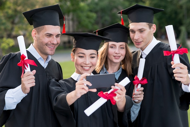 Portrait of group of students celebrating their graduation Free Photo