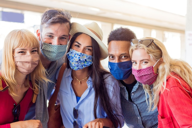 Portrait group of young happy friends wearing face mask during covid pandemic Premium Photo