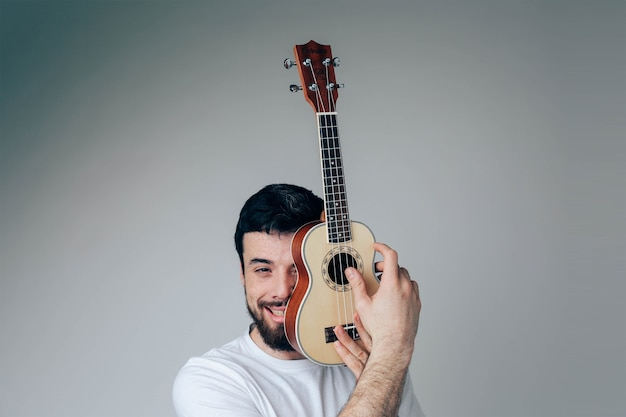 Portrait of guy cover face part with small ukulele Premium Photo