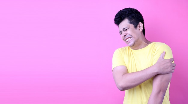 Portrait of a handsome asia man, holding his shoulder in pain on pink background in studio Premium Photo