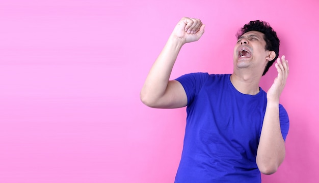 Portrait handsome asia man singing loud while standing  on pink background in studio Premium Photo