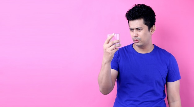 Portrait handsome asia men want to stop drinking  alcohol on pink background in studio Premium Photo