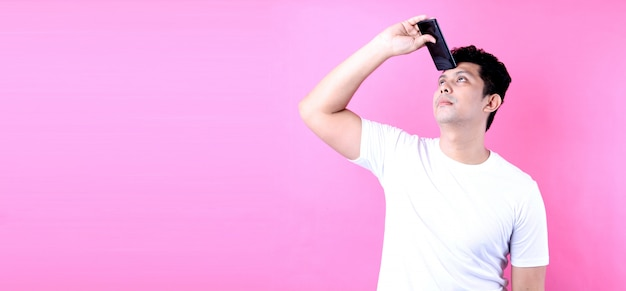 Portrait of handsome asian man with dreamy look, thinking while holding smartphone,on pink wall. Premium Photo
