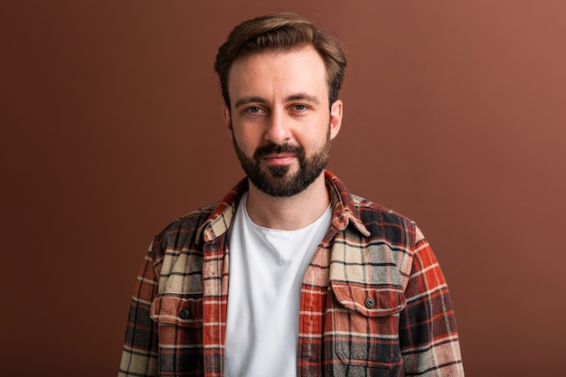 Portrait of handsome attractive stylish bearded man on brown Free Photo