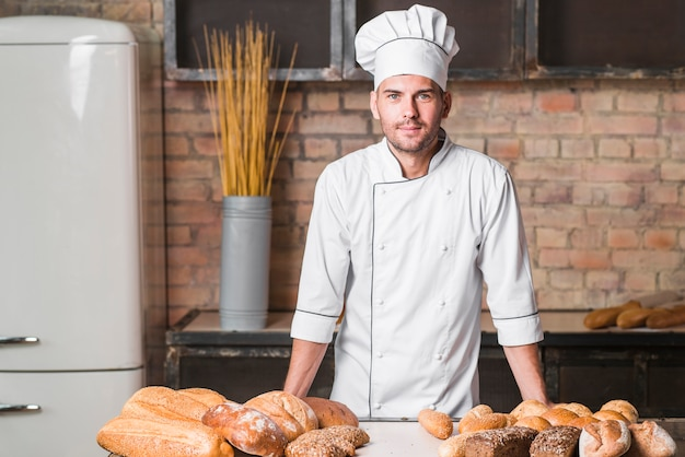 Portrait of handsome baker at the bakery with breads in bakery Free Photo