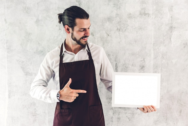Portrait of handsome bearded barista man small business owner smiling and holding empty board wooden frame with white mockup blank in a cafe Premium Photo