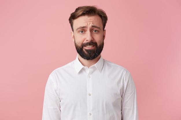 Ritratto di un bell'uomo barbuto che si rammarica di aver appena distrutto un castello di carte. aggrottare le sopracciglia e guardando la telecamera isolato sfondo rosa. Foto Gratuite