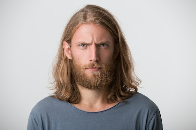 Portrait of handsome bearded young man with blonde long hair wears grey t shirt looks serious and confident isolated over white wall Free Photo