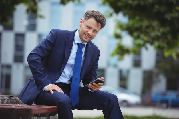 Portrait of handsome businessman holding mobile phone Premium Photo